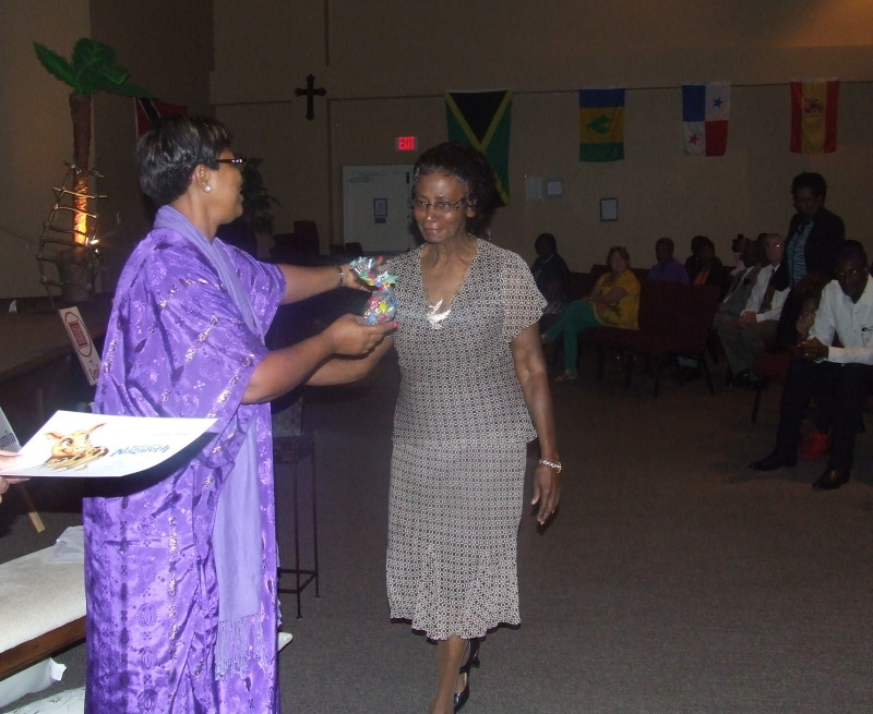 A lady dressed in biblical attire, purple, handing a gift to an older lady