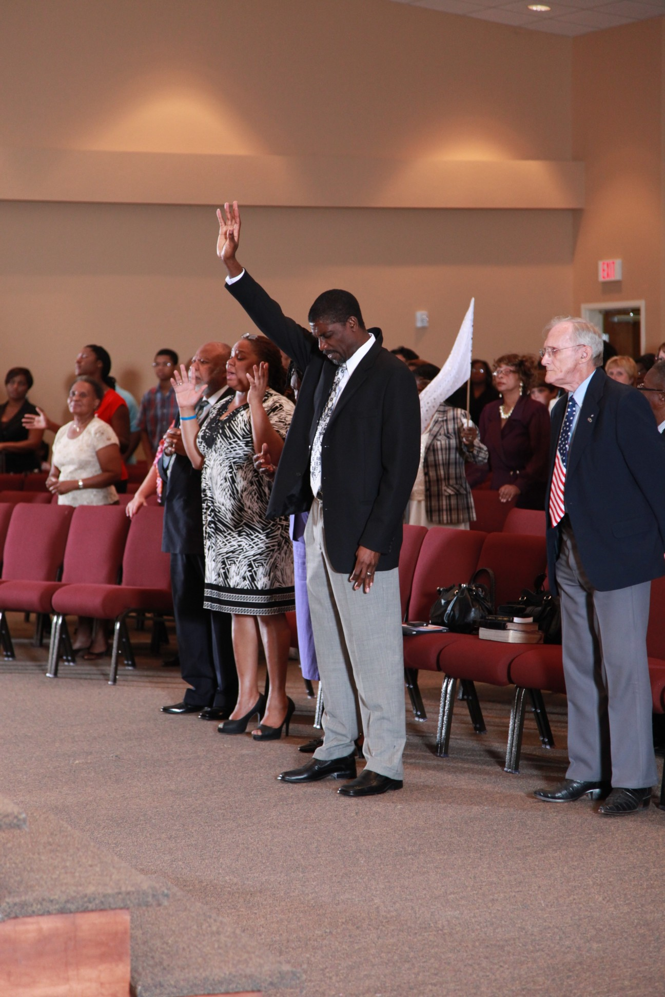 congregation standing and pastor ronald benjamin holding his right hand up in the air while his head is bowed