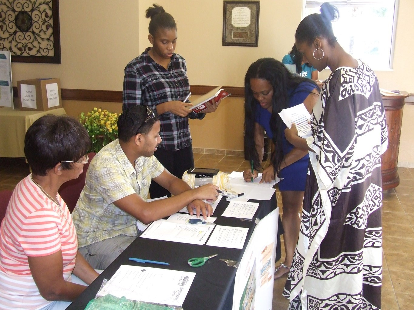 group of people at a table signing papers in the foyer entrance