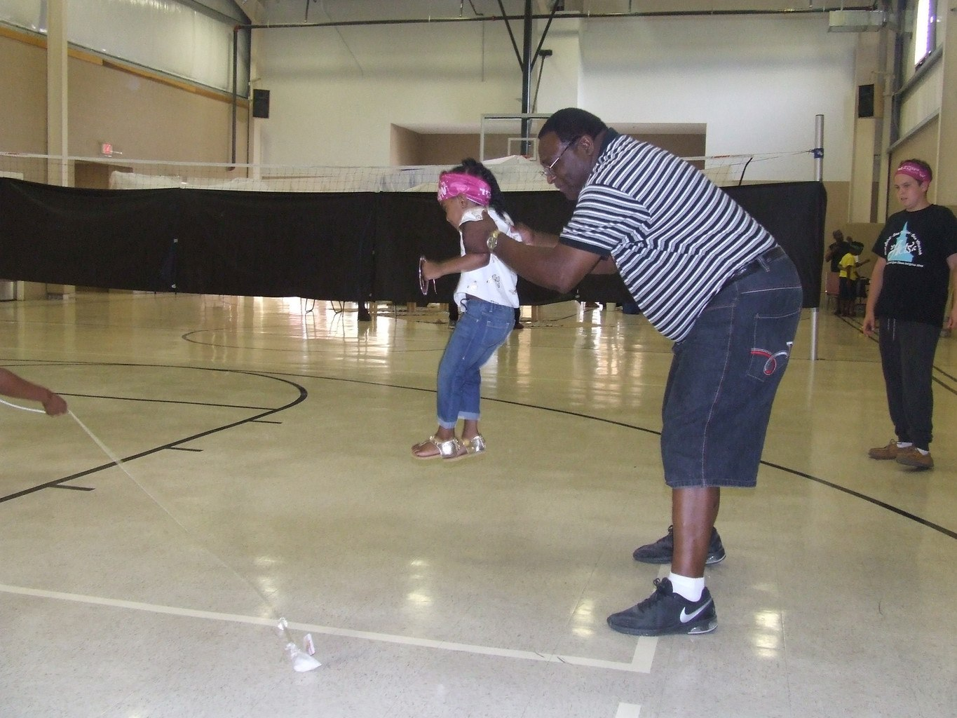 Minister Willie Bush help a child to do jump rope and another child looking on
