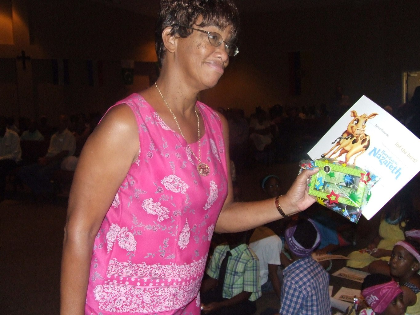 A lady smiling with her gift in her left hand